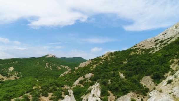 Légi kilátás dombos régióban hegyek a háttér a kék ég a felhők. Lelőtték. Repül át a hegyeken borított sűrű zöld erdő és szikla képződmények.