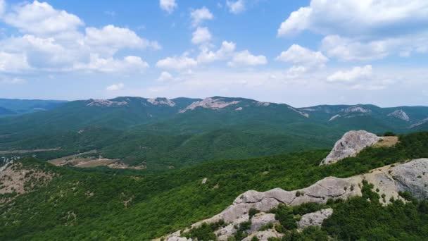 Légi kilátás hegyi sziklák egy hatalmas völgy kék felhős ég háttér. Lelőtték. Természetes lélegzetelállító táj zöld fákkal, sziklákkal és dombokkal.