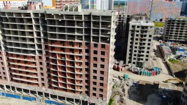 Top kilátás az építési telek a modern többszintes épületben. Indítvány. Tégla csupasz homlokzata többszintes épület építés alatt álló modern parkosított területen
