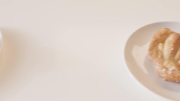 Detailní záběr talíře sladkého pečiva na bílém stole. Záběry ze skladu. Krásné a lahodné pečivo v kavárně. Croissanty, rohlíky, bochánky a jiné sladké pečivo