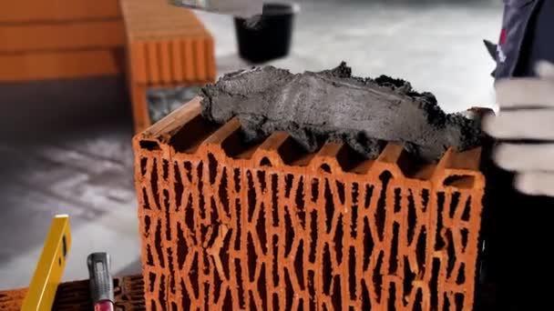 Dělník dává cement na cihlu na staveniště. Záběry ze skladu. Zedník pokládající cihly, aby udělal zeď, dává rýhu na cihlu