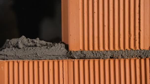 Detailní záběr cihlového špalku na beton. Záběry ze skladu. Zednické bloky z keramických červených cihel pro založení domu. Člověk pokládá cihlu na cement pro lepení se zbytkem zdiva