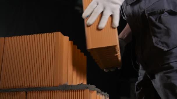 Detailní záběr muže, jak pokládá cihlový blok na beton. Záběry ze skladu. Stavitel dává červené cihly bloky na sebe drží spolu s cementem