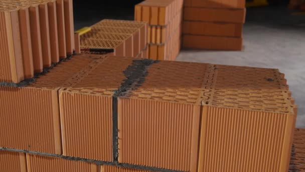 Detailní záběr zdiva z cihlových bloků v procesu výstavby. Záběry ze skladu. Červené keramické cihly bloky pro stavbu domu s pevnými tlustými stěnami