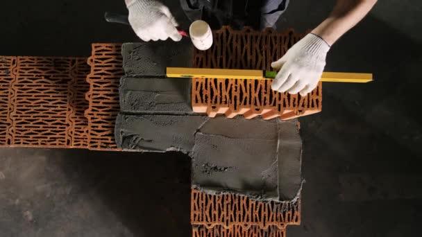 Közelkép az Építő segítségével szintező tégla munka. Készletfelvétel. Szakmai munka az építők a téglaépítés során. Építő korrigálja tégla során falazat szinttel és csapolás kalapáccsal