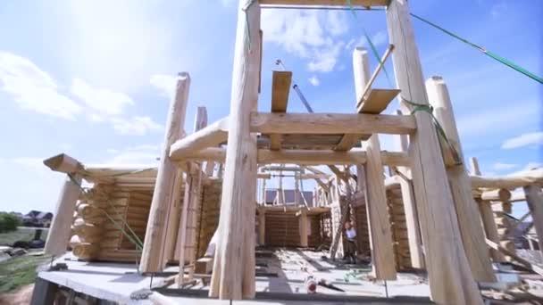 Neues Haus im Bau mit einem Schreiner, der im Rahmen vor blauem wolkenverhangenem Himmel steht. Clip. Blick von unten auf das unvollendete Holzhaus.