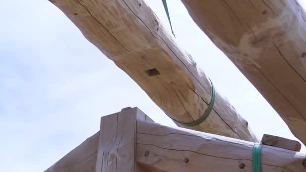 Část rámu dřevěného domu, detaily dřevěné příhradové konstrukce, budova z klád. Klip. Spodní pohled na zvednutý kulatý trám.