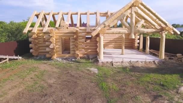 Antenne für den Bau des neuen Hauses im ökologischen Bereich in der Sommerzeit. Clip. Fassade des neuen Rohbaus aus Holzstämmen.