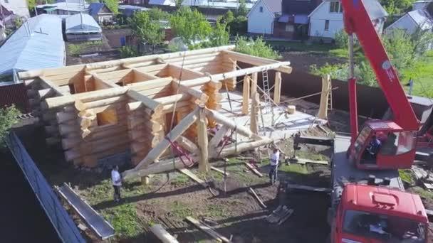 Konzept der Bauindustrie, Antenne von Arbeitern, die versuchen, das Dachelement des zukünftigen Hauses zu installieren. Clip. Kranmaschine hebt das Dachdetail von Holzstämmen.