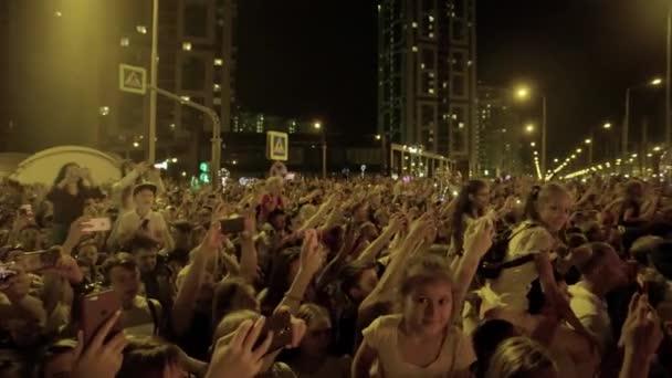 Jekatěrinburg, Rusko-srpen, 2019: Dav lidí se shromáždil na oslavu na pozadí městských světel. Umění. Událost na počest dne města a lidí shromážděných na náměstí v létě večer