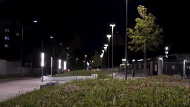 öffentliche Parkinfrastruktur und Nachtbeleuchtung. Archivmaterial. Mann läuft durch grüne Gasse im Stadtpark in der Nähe heller Straßenlaternen.