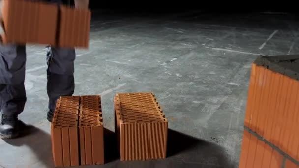 Průmyslový zedník pokládající cihly na beton při stavbě zdí. Záběry ze skladu. Detailní záběr muže v ochranných rukavicích uvedení těžké cihly blok tvořit vrstvu.