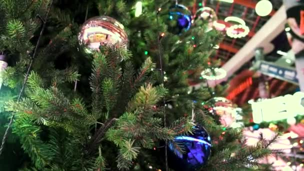 Close up of an artificial Christmas tree in a shopping center or mall. Concept. Christmas and New Year decorations, colorful balls and green spruce branch.