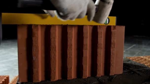Průmyslové zázemí, dělník v rukavicích používající kladivo pro kladení cihel do cementu. Záběry ze skladu. Detailní záběr muže pomocí úrovně a kladivo, aby se rovná řada cihel.