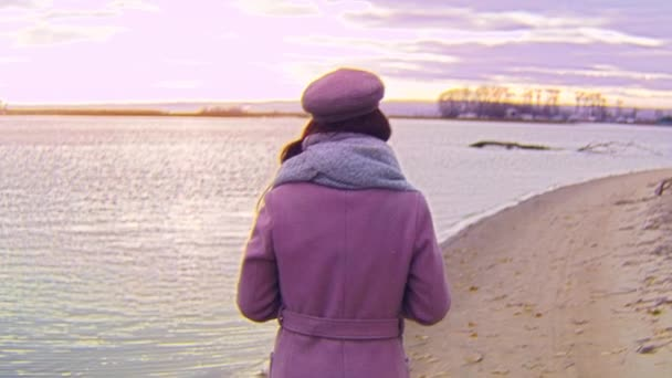 Rear view of attractive woman walking on background of sunset landscape of coast. Stock footage. Beautiful coastal landscape in colors of sunset and young woman walking on beach in autumn