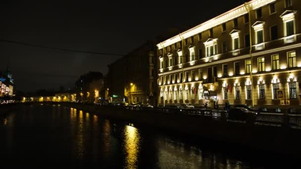 Beautiful view of city canal with evening lights. Concept. Yellow city lights illuminating the streets by canal reflected in water. Beautiful night city in light of lanterns and garlands by canal