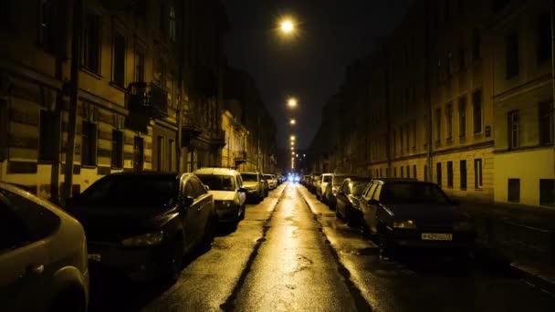 Europäische Straße im Licht der gelben Laternen bei Nacht mit parkenden Autos. Konzept. Gerade schöne Straße mit Wohnhäusern und geparkten Autos, nachts beleuchtet von gelben Laternen