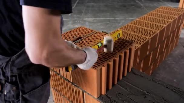 Detailní záběr průmyslového pracovníka, který vyrábí zeď s maltou a cihlami, pomocí kladiva a rovinného nástroje. Záběry ze skladu. Mužské ruce stavět vnější stěny, pomocí kladiva pro kladení cihel v cementu.