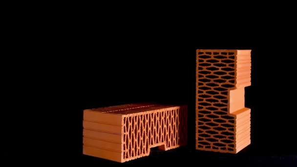 Small pile of red ceramic blocks moving slowly isolated on black background, materials for building construction. Stock footage. Red perforated bricks against black wall.