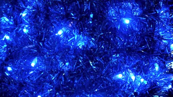 Ünnepi fényes karácsonyi háttér koszorú és villogó izzók. Fogantatás. Közelkép a szilveszteri kék tinsel, lakberendezési.