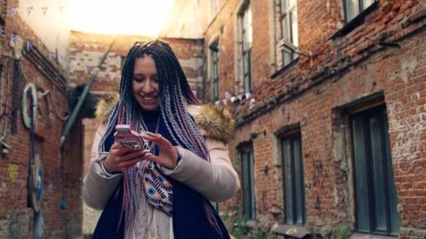Giovane hipster donna sorride e si siede sul suo telefono ...