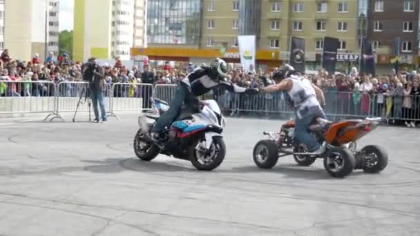 Yekaterinburg, Russia-August, 2019: Quad bike rider and motorcyclist perform stunts. Action. Professional riders on motorcycle transport perform tricks on site located in city for Moto festival