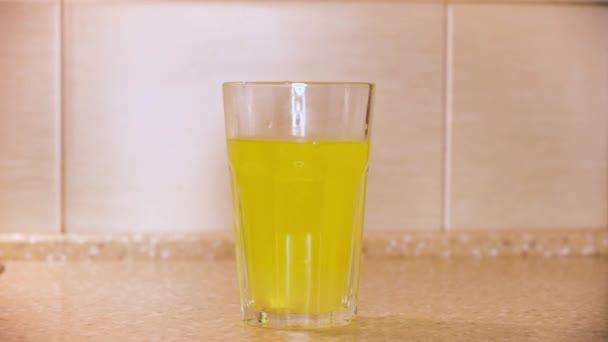 Großaufnahme eines Wasserglases und einer Brausetablette, Großaufnahme. Konzept. Runde gelbe Schmerztablette, medizinisches Konzept, wasserlösliche Vitamine.