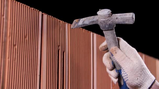 Close up of man hands holding hammer and using it to make an oblong hole on black background. Stock footage. Construction worker demolishing hole at brick wall with a hammer.