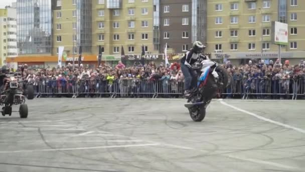 Yekaterinburg, Russia-August, 2019: Motorcyclists perform tricks at freestyle show. Action. Professional motorcyclists perform stunts on background of crowd of people behind fence