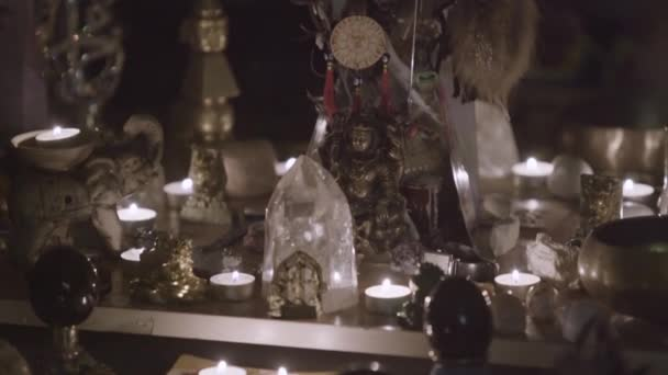 Nahaufnahme des Feng Shui-Altars zu Hause im Wohnzimmer auf dem Tisch. Kunst. Attraktives Wohlstands- und Wohlstandskonzept, Kristallcluster, goldene Buddha-Figur und Kerzen.