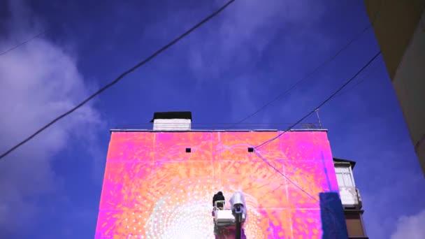 Lényegében egy művész felemelő darut használ, hogy lélegzetelállító graffitiket rajzoljon a kék felhős égbolt hátterére. Művészet. Street art koncepció, ember egy spray festék.