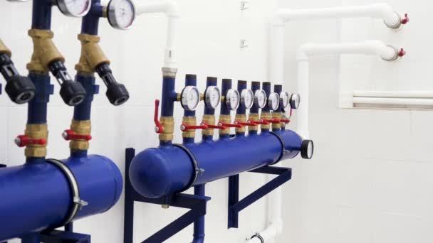 Nahaufnahme von Manometer, Rohren und Armaturenventilen der Heizungsanlage in einem neuen weißen Heizungsraum. Archivmaterial. Heizungsraum und Ausrüstung im Mehrfamilienhaus.