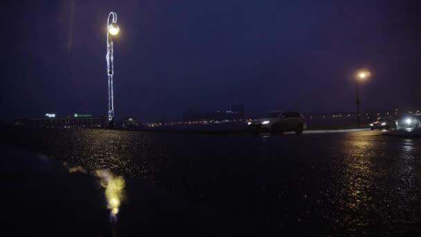 Schöne nächtliche Stadt mit Verkehr und Straßenbeleuchtung nach Regen. Reise. Nächtliche Stadt mit Autoverkehr und Straßenbeleuchtung, die sich nach Regen auf nassem Asphalt spiegelt