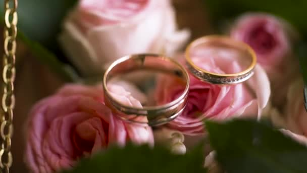 Close up of a pair of wedding rings in a decorated box with pink tender rose flowers, love and family concept. Action. Two golden yellow wedding rings lying on pink rose buds with green petals.