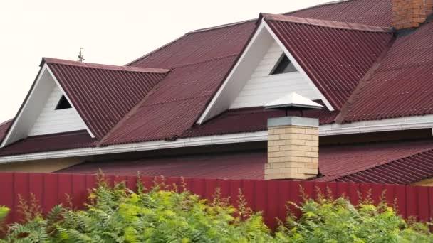 Moderní střecha pokrytá dlaždicemi červené barvy na šedém pozadí oblohy, střešními materiály a stavební koncepcí. Záběry ze skladu. Moderní fasáda domu.