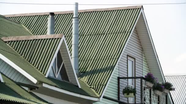 Moderní střecha pokrytá dlaždicemi zelené barvy na šedém pozadí oblohy, střešními materiály a stavební koncepcí. Záběry ze skladu. Moderní fasáda domu.