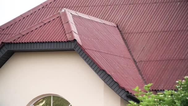 Krásná střecha městského domu s červenými střešními taškami na zakaleném pozadí oblohy. Akciová fotáž. Fasáda nového obytného domu, architektonický koncept.