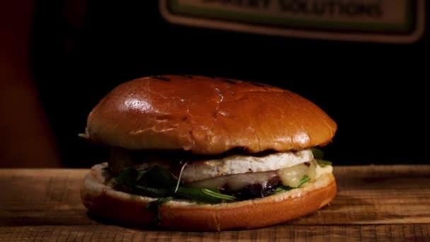 Close up of home made tasty burger on wooden table, gastronomy and foodporn concept. Záběry ze skladu. Šťavnatý sendvič s hovězím masem, sýrem, salátem a cibulí.