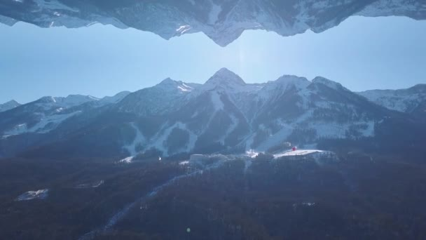 Breathtaking landscape of snowy mountains with mirror reflection effect. Clip. High hills covered by forest in winter season and the ski resort, inception theme.