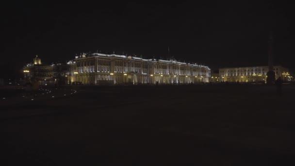 Noční pohled na malebnou osvětlenou architekturu centra města Petrohradu, majestátní Zimní palác s lidmi procházejícími se kolem. Pohyb. Slavný Hermitage stavět na černém pozadí oblohy.