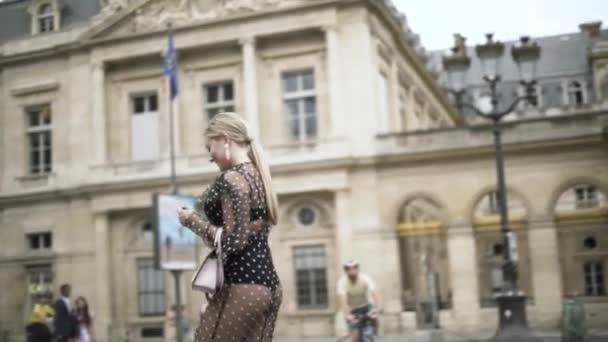 Boční pohled na neuvěřitelné blondýny v černých šatech chůze a pózování v blízkosti krásné historické budovy. Akce. Mladá žena s dlouhým rovným culíkem a bílou malou spojkou.