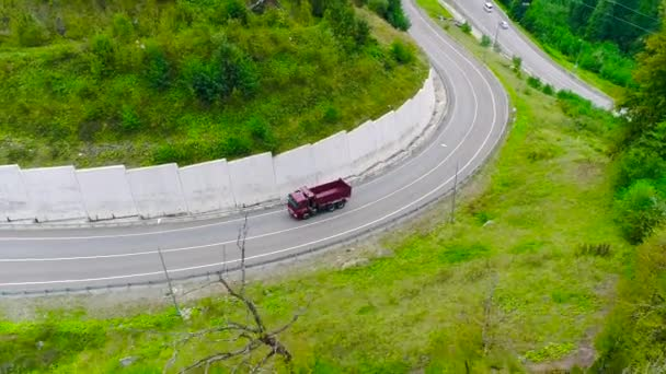 A teherautó a szerpentin úton halad. Jelenet. Top kilátás teherautó mentén szerpentin felfelé a háttérben a zöld erdő és a város távolban