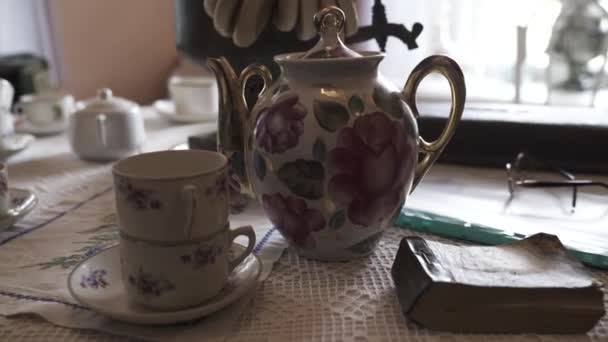Antique dishes of Russian life. Stock footage. Service set with porcelain cups and teapot on background of samovar. Tea set of Russian life