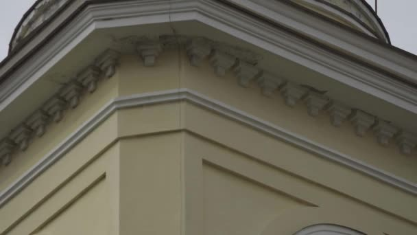 Nahaufnahme der Fassade des Turms und des Kreuzes auf der Kuppel der Kirche. Archivmaterial. Schönes Kreuz erhebt sich auf goldener Kuppel der Kirche vor wolkenverhangenem Himmel