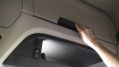 Fotografie Nahaufnahme einer Kabine eines modernen LKW mit Handschuhfach, Transportkonzept. Szene. Männliche Hand schließt Handschuhfach und legt seine Brieftasche ins Regal.