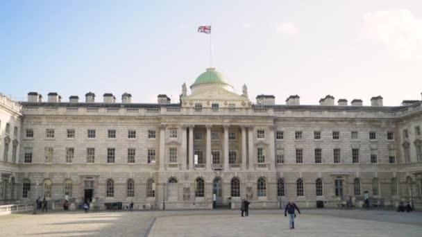 Nádvoří v bílém paláci. Akce. Turisté procházka na náměstí na pozadí fasády bílého evropského paláce s vlajkou Velké Británie