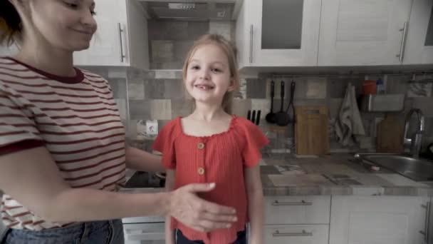 Šťastná matka líbá dceru doma v kuchyni. Akce. Trávit čas s rodinou, milující maminka dává pusu na tvář její roztomilé dívce, koncept lásky.