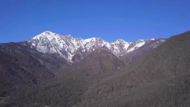 Horní pohled na horskou krajinu s lesy a zasněženými vrcholky. Klip. Krásný malebný vrchol zalesněných hor se sněhovou čepicí na pozadí jasné modré oblohy na jaře