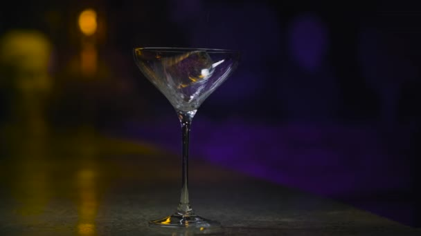 Eiswürfel fällt ins leere Glas. Archivmaterial. Eiswürfel fällt ins schöne leere Martini-Glas auf Neonhintergrund der Theke. Cocktailbar