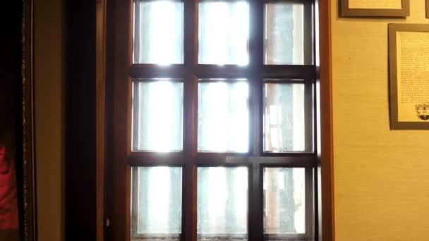 Prohlížení uvnitř historického muzea, skleněné okno s dřevěnými přepážkami a starobylými dokumenty zavěšenými na zdi v rámečcích. Záběry ze skladu. Rekonstrukce historických událostí a míst v muzeu.